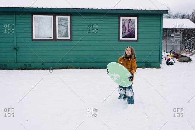 Boy holding snow sled in backyard