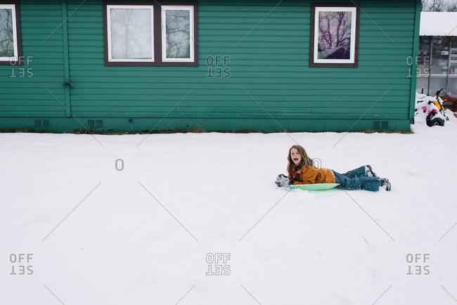 Boy lying on snow sled in backyard