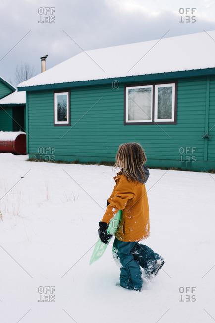 Boy walking with sled in winter yard