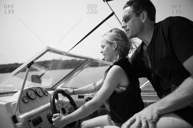 Father teaching daughter to drive a boat