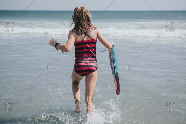 Girl walking out to the ocean with a boogie board