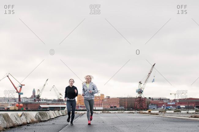Two female running friends running along dockside