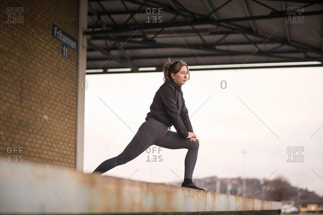 Female runner leaning forward stretching on warehouse platform