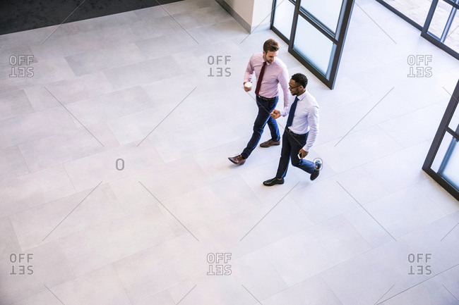 High angle view of two businessmen arriving in office atrium