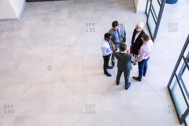High angle view of businesswoman and men having discussion in office atrium