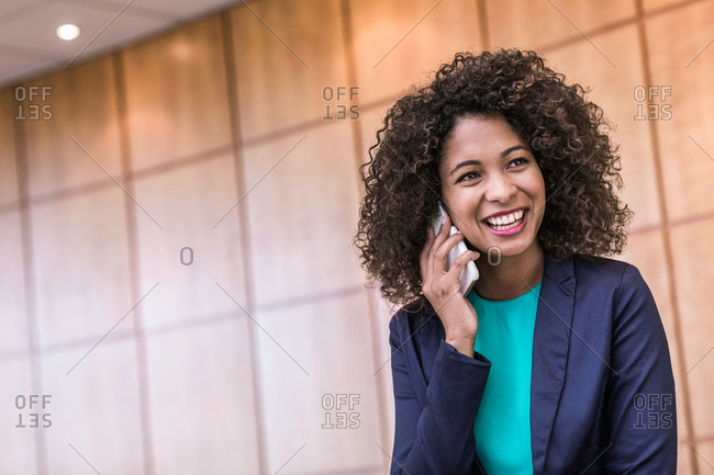 Young businesswoman talking on smartphone in office
