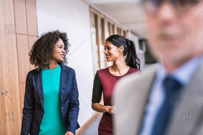 Two young businesswomen talking at office