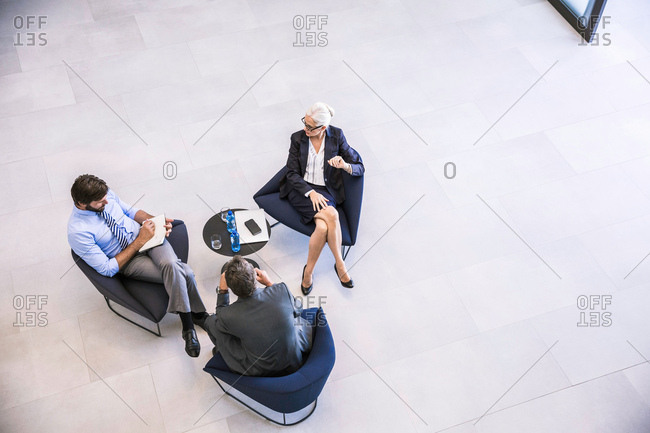 High angle view of businesswoman and men meeting in office atrium