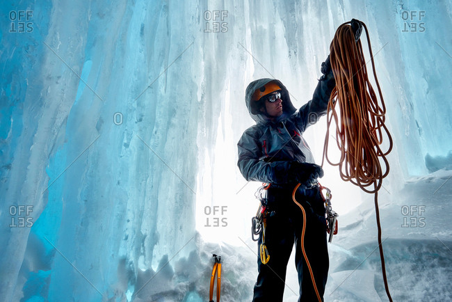 Man in ice cave preparing climbing rope, Saas Fee, Switzerland