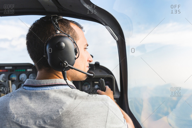 Pilot in cockpit of aircraft, in flight