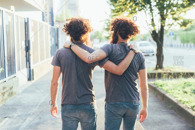 Rear view of identical male adult twins strolling on sidewalk