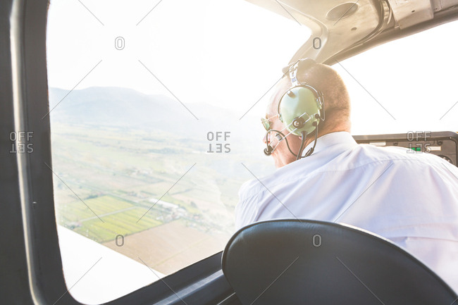 Rear view of pilot in cockpit of aircraft in flight