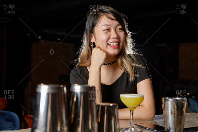 Woman at bar with cocktail looking away smiling