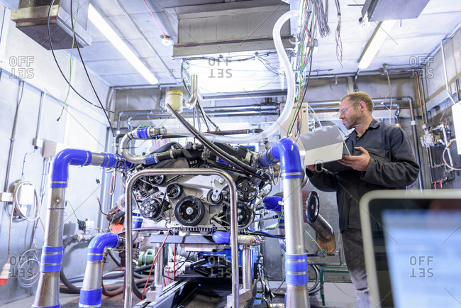 Engineer testing exhaust system on engine in factory