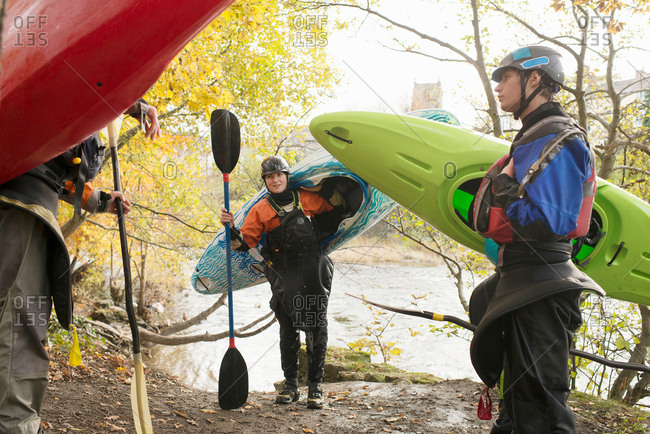 Male and female kayakers carrying kayaks on banks of  River Dee