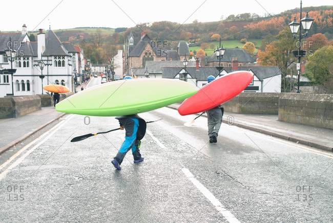 Two kayakers carrying kayaks on bridge over River Dee, Llangollen, North Wales