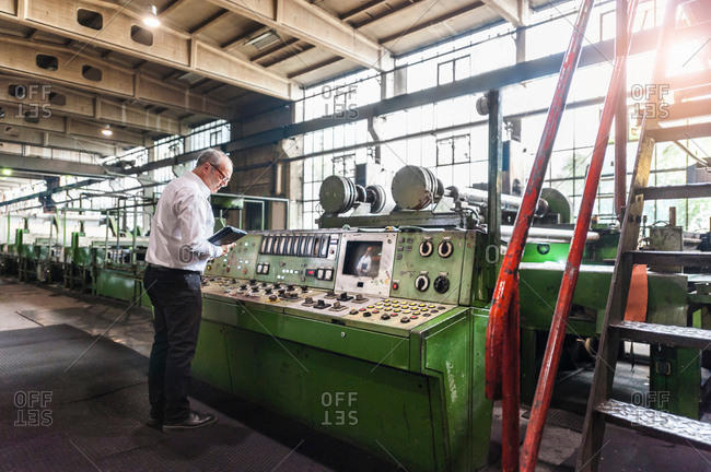 Man inspecting control panel in tire manufacturing plant, Ballenstedt, Germany