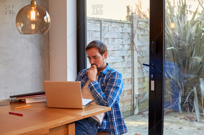 Mid adult man reading laptop update at dining table