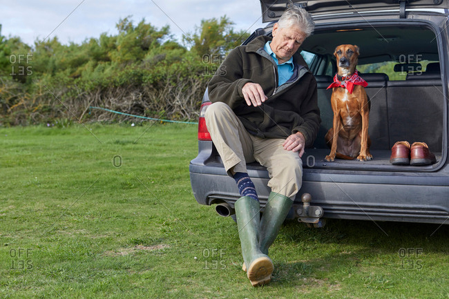 Man and dog sitting in car boot removing wellington boots