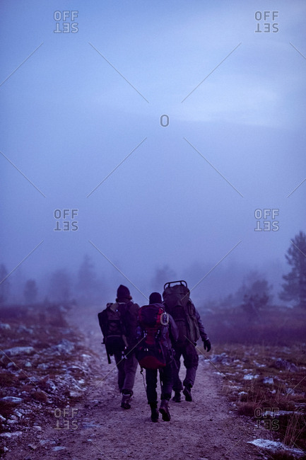 Hikers crossing rocky field at dusk, Sarkitunturi, Lapland, Finland
