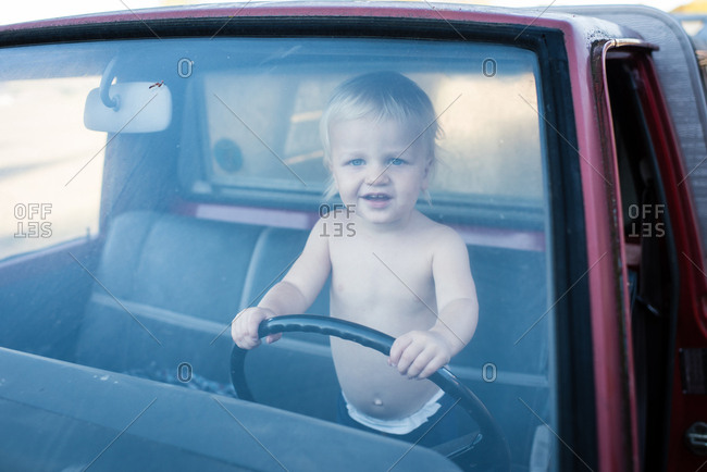 Portrait of male toddler standing in truck holding steering wheel