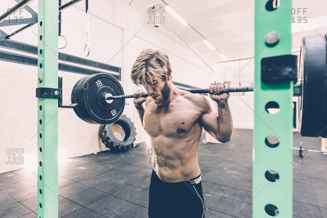 Young male cross trainer weightlifting barbell in gym