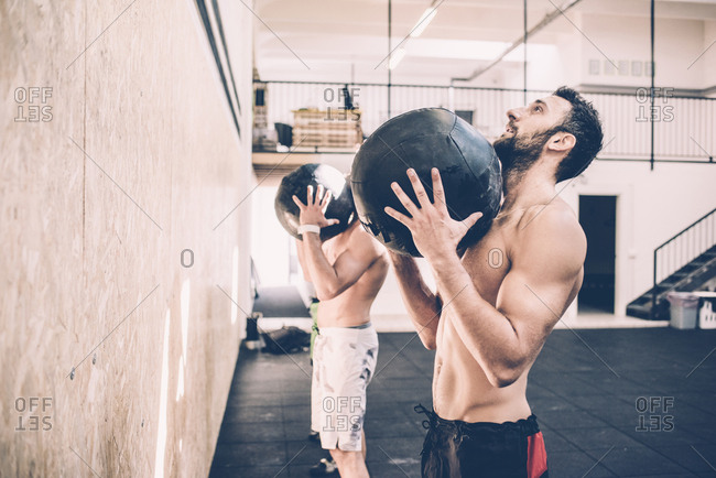 Two male cross trainers holding exercise balls in gym