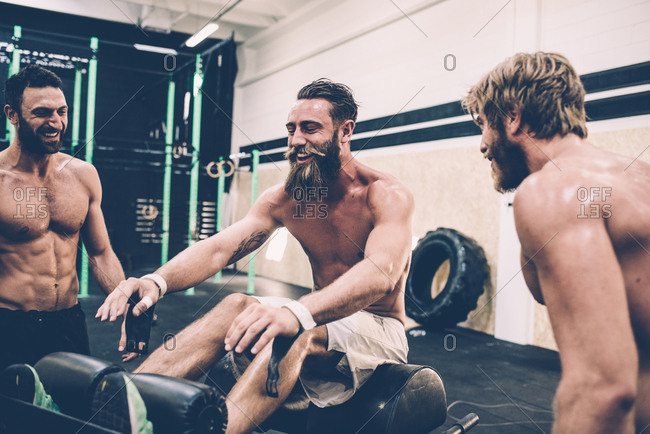 Three male cross trainers chatting in gym