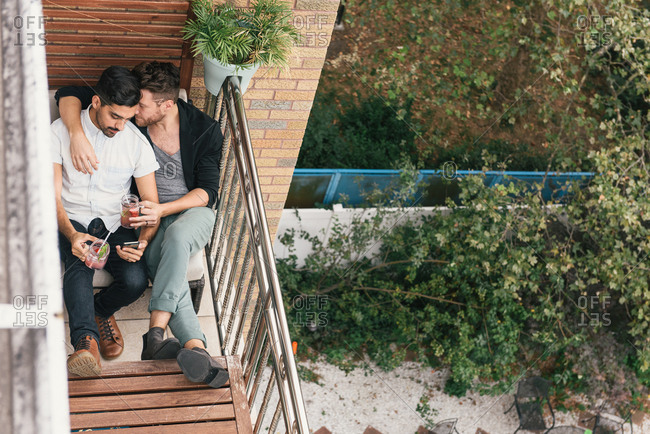 Young male couple on apartment balcony reading smartphone