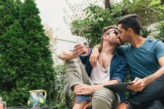 Romantic young male couple sitting in garden kissing