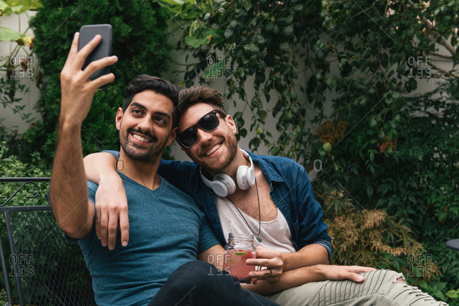 Young male couple sitting in garden taking smartphone selfie
