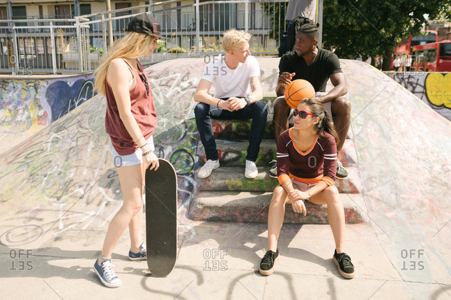 Four male and female basketball and skateboarding friends sitting chatting in city skatepark
