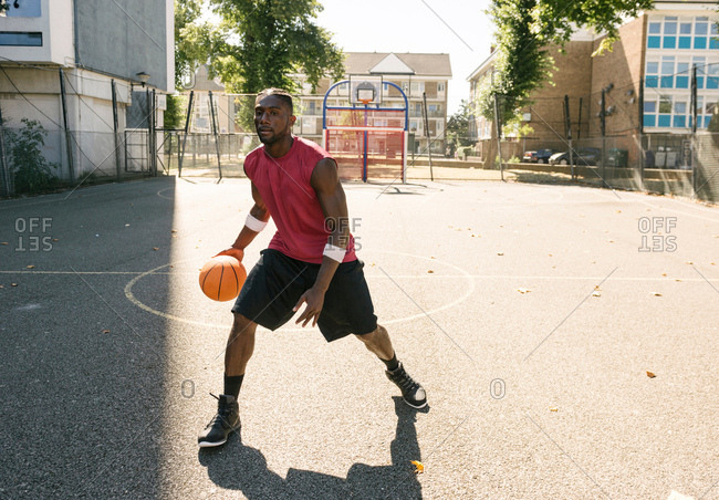 Young man practicing on basketball court