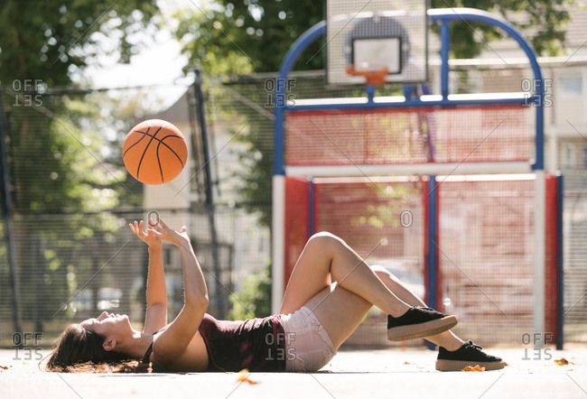 Young woman lying on basketball court throwing ball