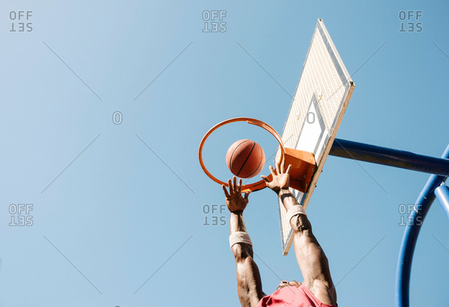 Young male basketball player throwing ball in basketball hoop