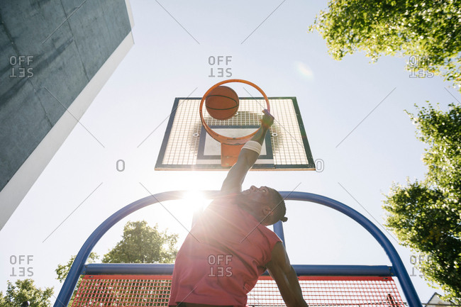 Young male basketball player throwing ball in sunlit basketball hoop