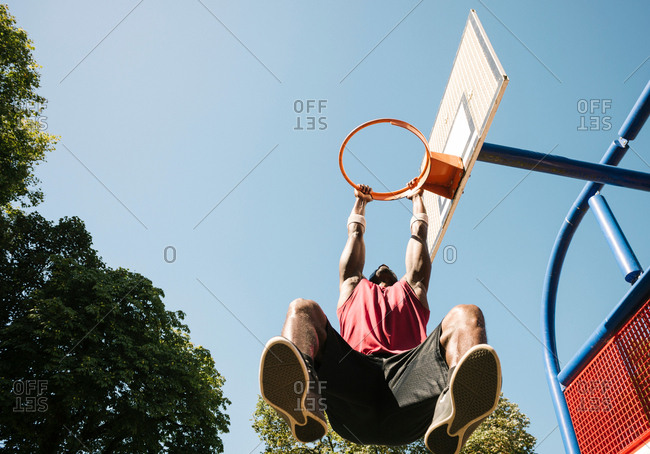 Young male basketball player hanging from basketball hoop