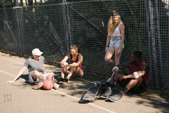 Four adult skateboarder friends sitting chatting on basketball court