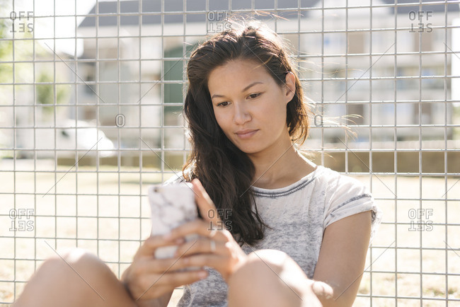 Woman reading smartphone updates by wire fence