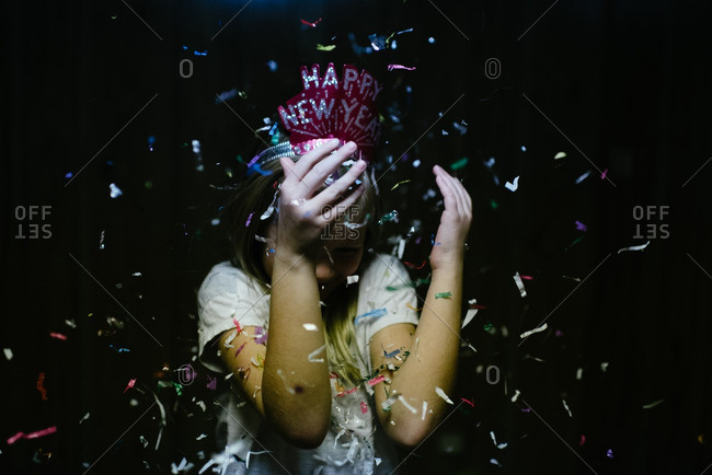 Girl hiding face from New Year's confetti