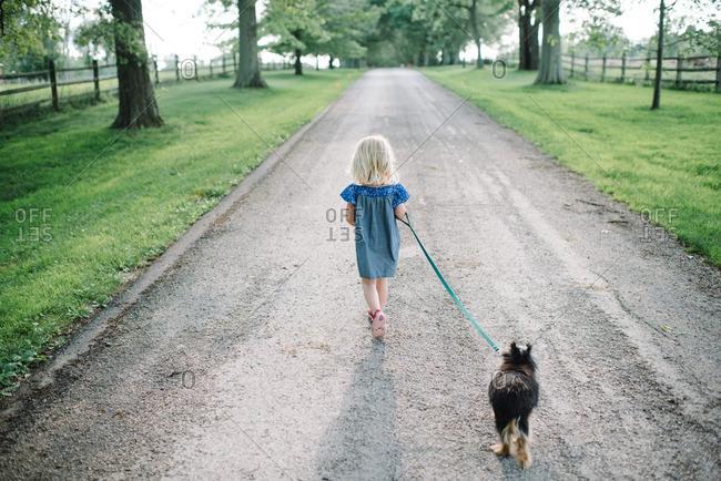 Girl walking dog down country lane