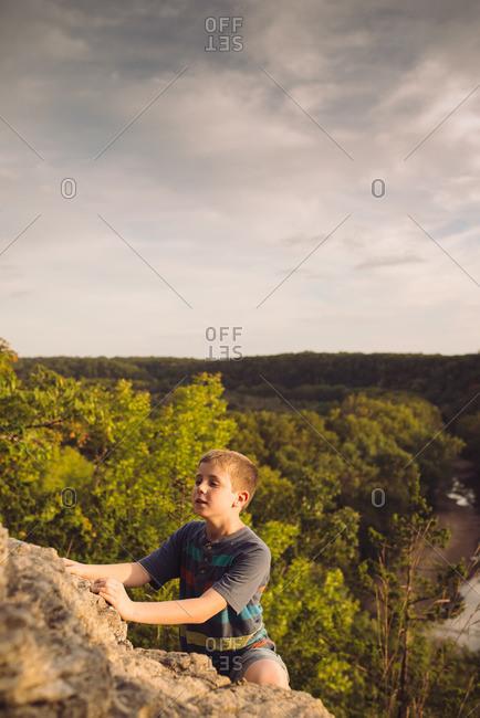 Boy climbing up a rock face