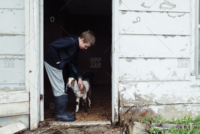 Young boy petting a goat in doorway of barn