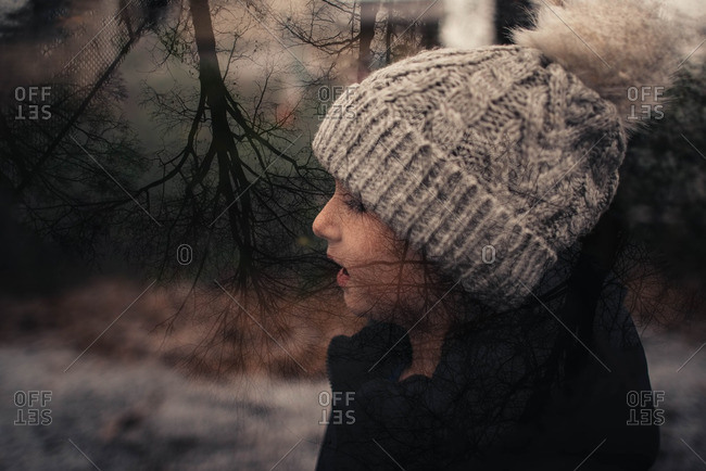 Girl in double exposure with bare trees