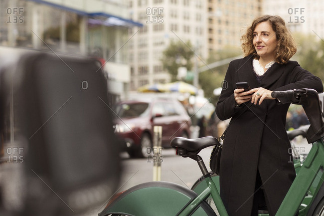Woman using mobile phone while standing by bicycle rack in city