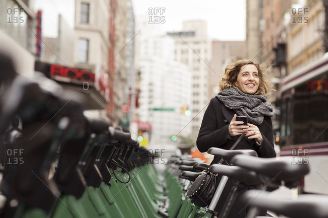 Woman holding mobile phone standing by bicycle rack in city
