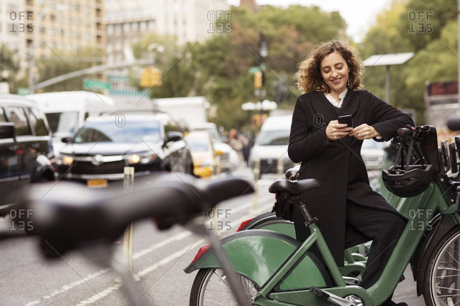 Smiling woman using mobile phone while standing by bicycle rack in city