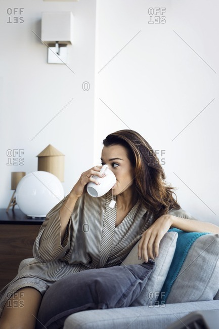 Woman drinking tea while relaxing on armchair at home