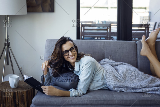 Woman looking away while reading book on sofa at home