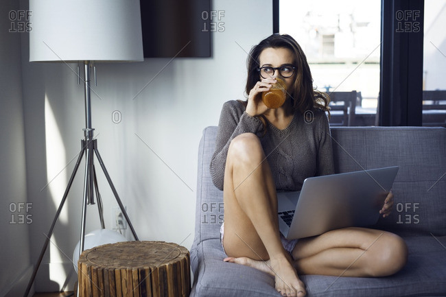 Woman drinking while using laptop computer on sofa